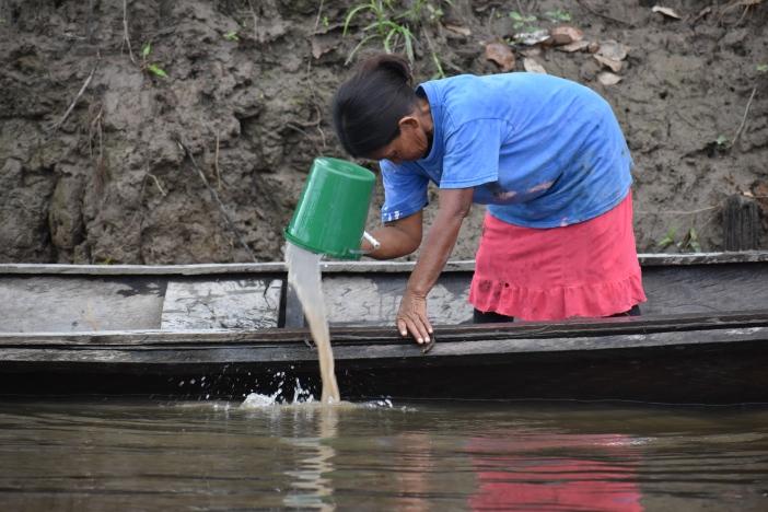 Una mujer retira agua de su barquita a la llegada a la Comunidad Nazareth (Leticia, Colombia) Foto Marta Isabel González Álvarez/CIDSE & REPAM